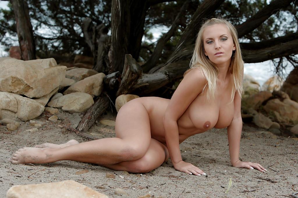 Голая блондинка с большими дойками позирует у дерева и на камне 13 фото