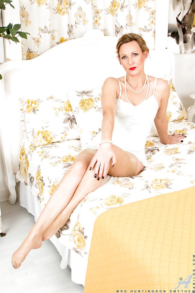 Накрашенная мамка в белом белье позирует и демонстрирует дырку в цветочной комнате 1 фото