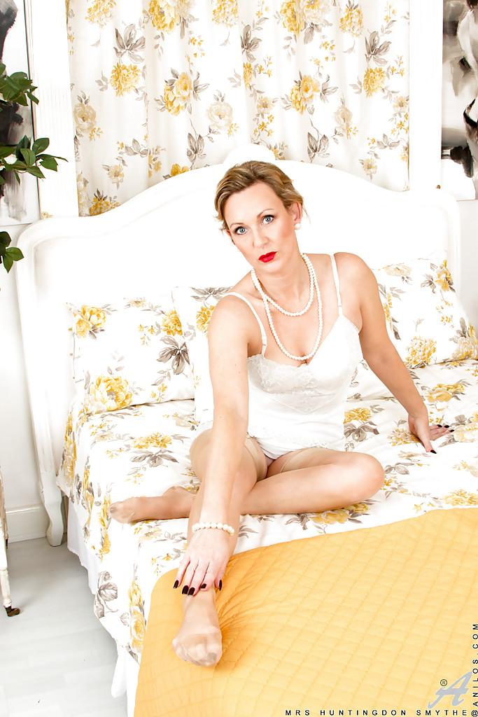 Накрашенная мамка в белом белье позирует и демонстрирует дырку в цветочной комнате 2 фото