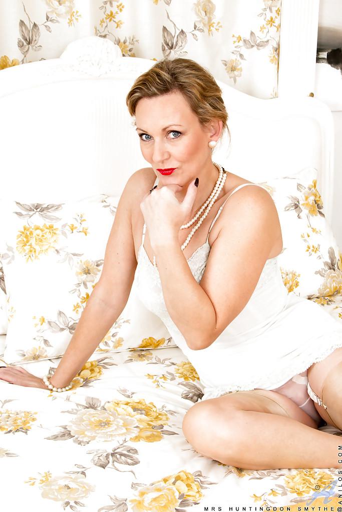 Накрашенная мамка в белом белье позирует и демонстрирует дырку в цветочной комнате 4 фото