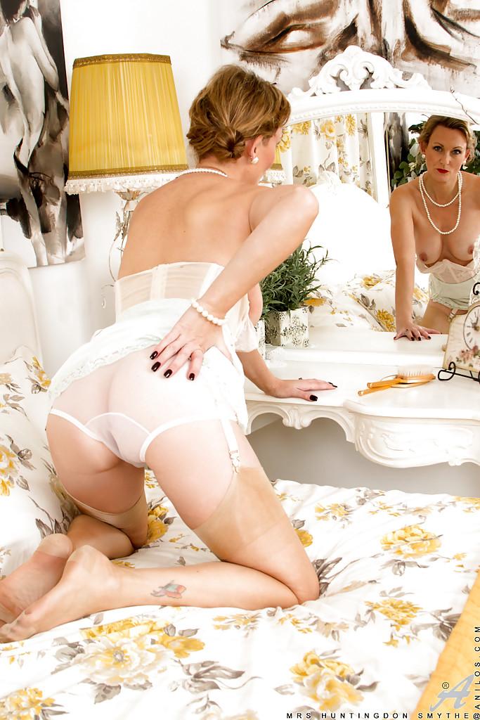 Накрашенная мамка в белом белье позирует и демонстрирует дырку в цветочной комнате 10 фото