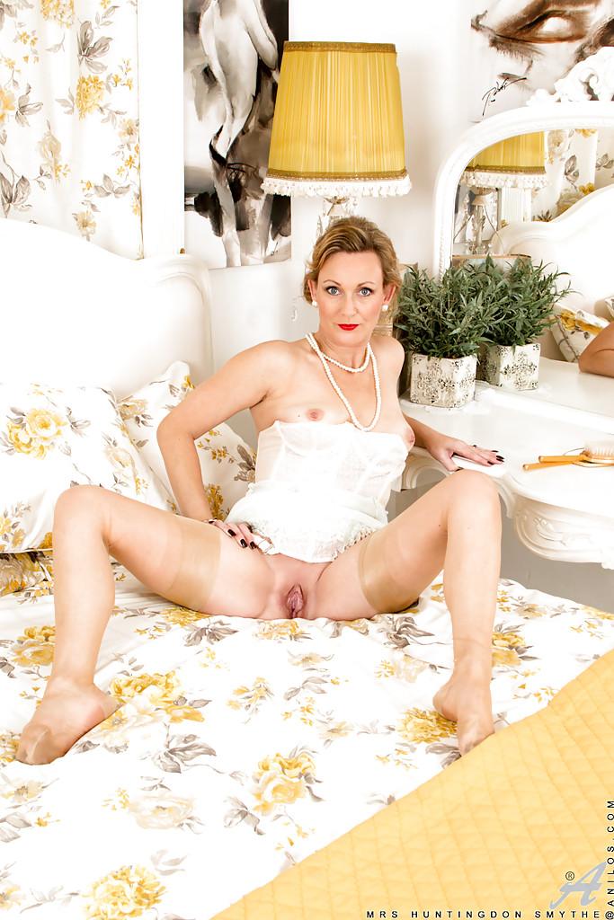 Накрашенная мамка в белом белье позирует и демонстрирует дырку в цветочной комнате 16 фото