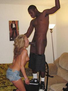 Негр встал на стул, чтобы блондинке было удобнее делать минет