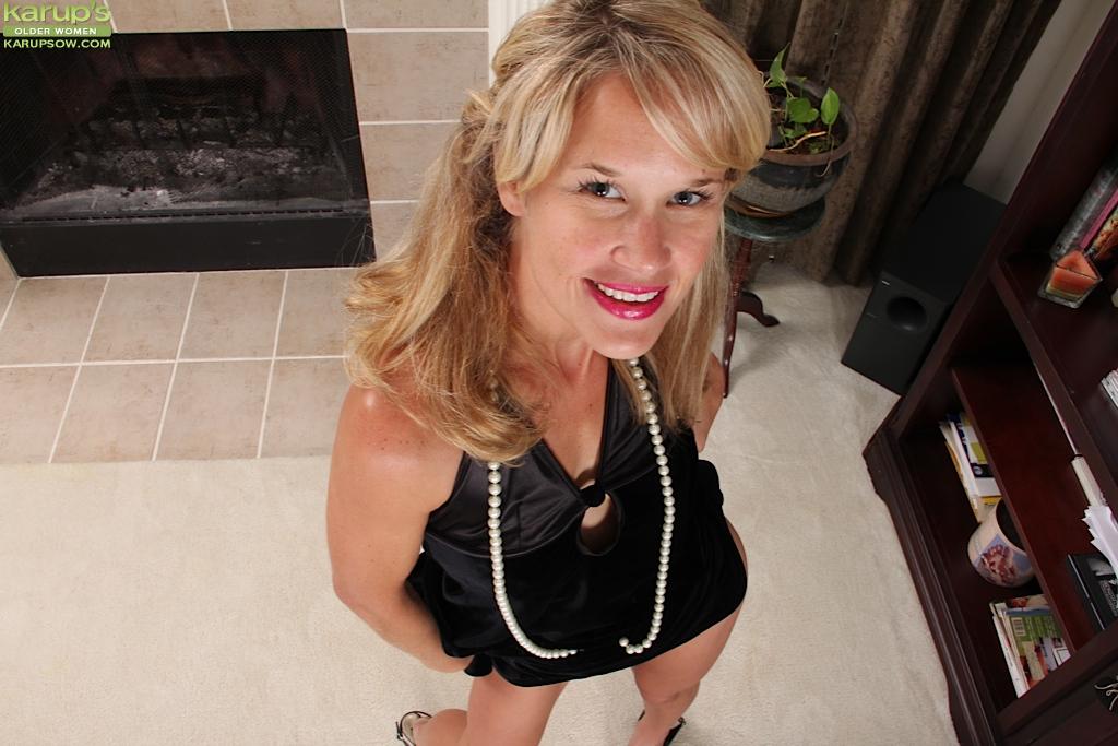 Зрелая женщина в чёрном платье раздевается у камина 1 фото
