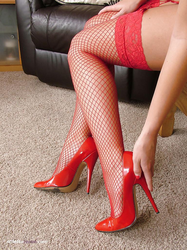 Блондинка в красном белье и чулках примеряет новые туфли на тумбе 16 фото