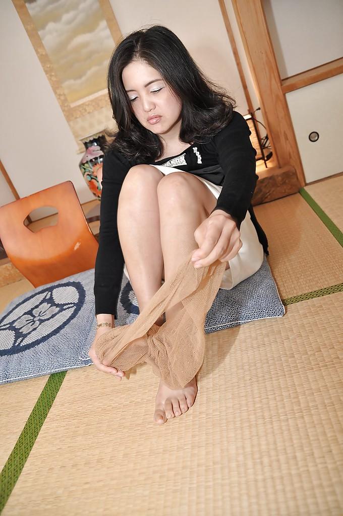 Зрелая азиатка с черными волосами раздевается на полу 4 фото