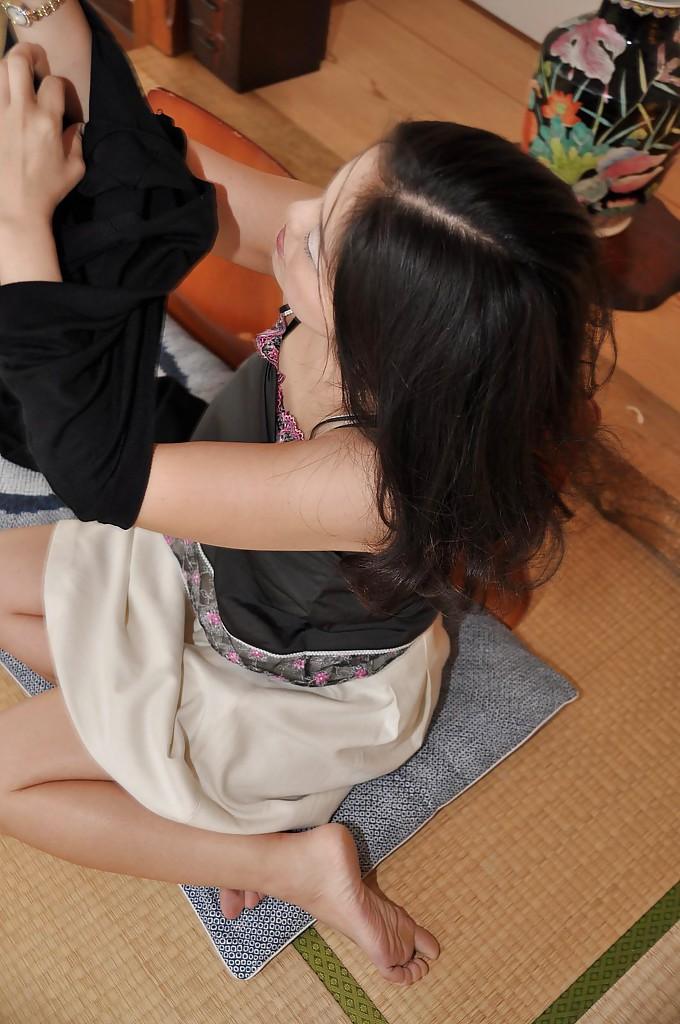 Зрелая азиатка с черными волосами раздевается на полу 6 фото