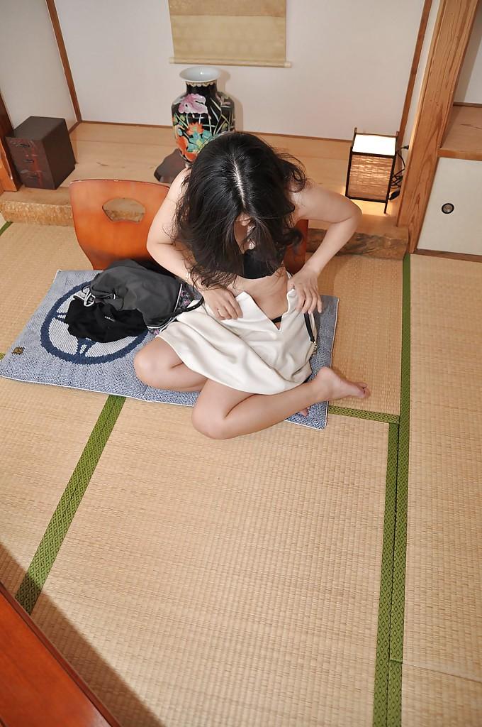 Зрелая азиатка с черными волосами раздевается на полу 9 фото