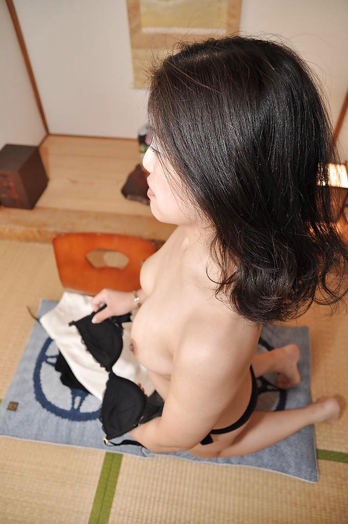 Зрелая азиатка с черными волосами раздевается на полу 11 фото