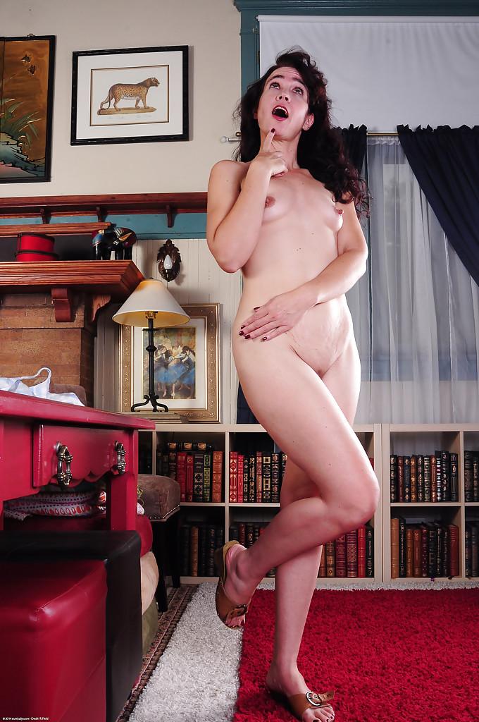 Зубастая мамка раздевается и показывает киску на красном столе 9 фото