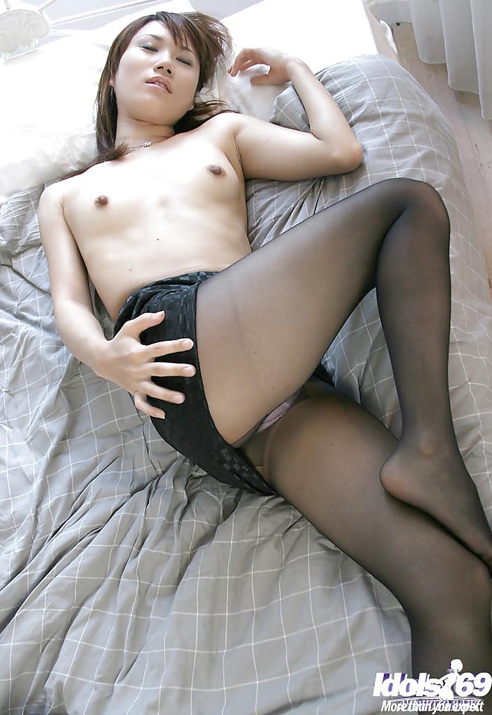 Японка в розовых трусиках и колготках обнажается в постели 13 фото