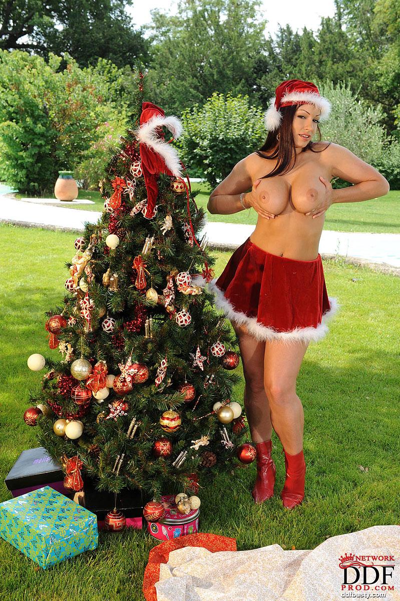 Снегурочка с большими сиськами в красном костюме стоит возле ёлки 8 фото