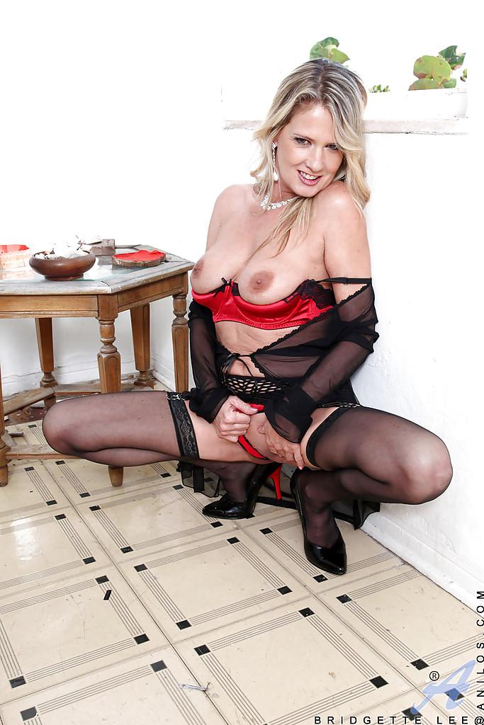Зрелая дама в чулках мастурбирует розовым вибратором в спальне 4 фото