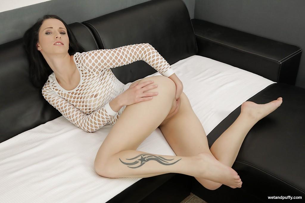 Худощавая брюнетка в сетчатом платье мастурбирует кистью на диване 10 фото