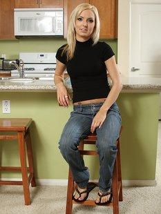 Худая блондинка раздевается у кухонного стола