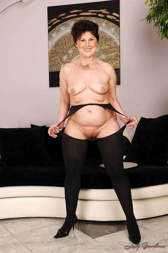 Бабуля в чулках и с небритой мандой раздевается возле дивана 7 фото