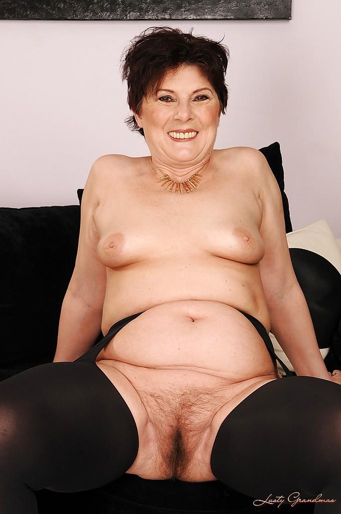 Бабуля в чулках и с небритой мандой раздевается возле дивана 10 фото
