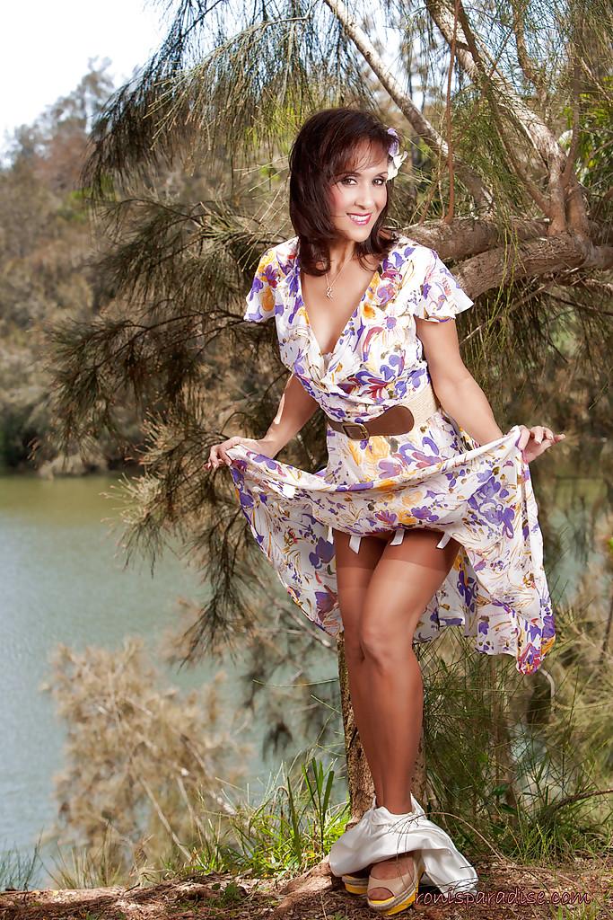 Дамочка в летнем платье раздевается в тени дерева на берегу реки 1 фото