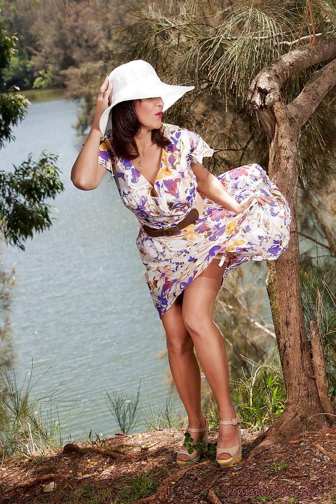 Дамочка в летнем платье раздевается в тени дерева на берегу реки 2 фото