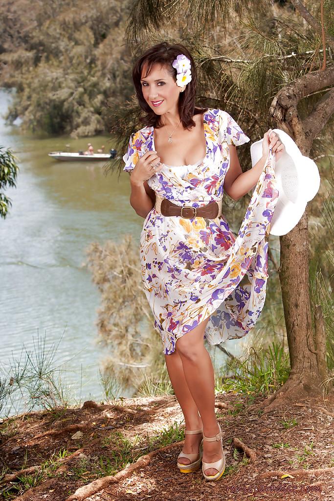 Дамочка в летнем платье раздевается в тени дерева на берегу реки 4 фото