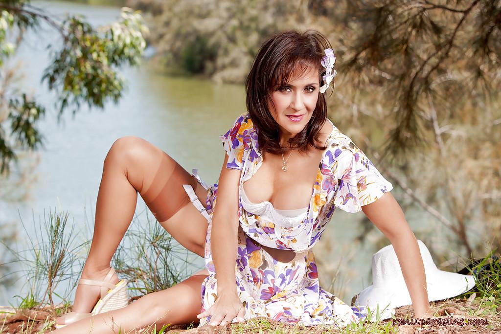Дамочка в летнем платье раздевается в тени дерева на берегу реки 5 фото