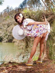 Дамочка в летнем платье раздевается в тени дерева на берегу реки